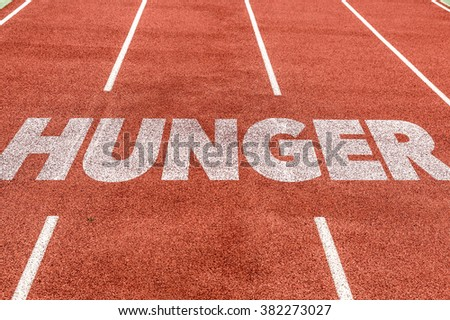 Hunger written on running track - stock photo