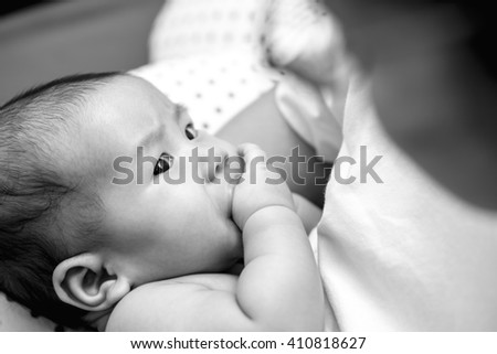Hungry Asian baby sucking his fingers instead of mother breastfeeding - stock photo