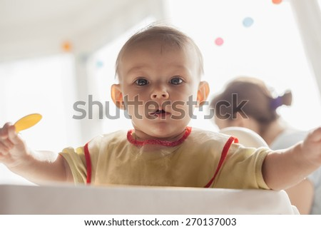 Hungry Baby Boy Holding A Spoon And Waiting For Food - stock photo