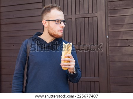 Hungry bearded customer eating delicious fast food: hotdog. Outside photo - stock photo