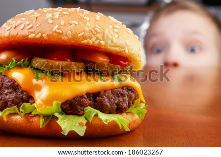 Hungry boy is staring and smelling a burger on wooden table - stock photo