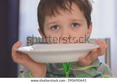 Hungry boy with beautiful eyes waiting for dinner. Holding empty plate in his hands - stock photo