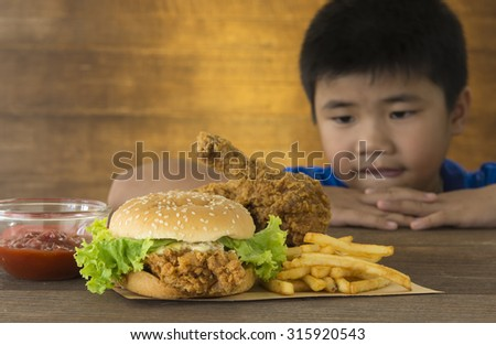 hungry children stared want to eat a burger on a wooden table. - stock photo