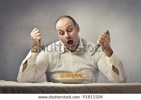 Hungry fat man eating spaghetti - stock photo