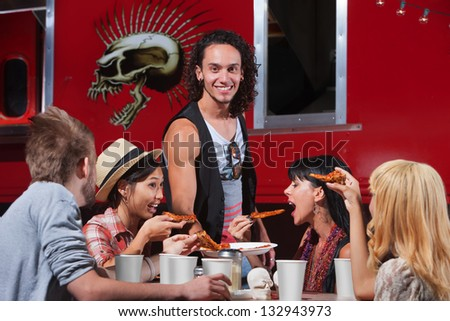 Hungry friends sharing slices of pizza at cafe - stock photo