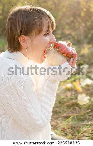 Hungry girl biting a pumpkin on Halloween - stock photo