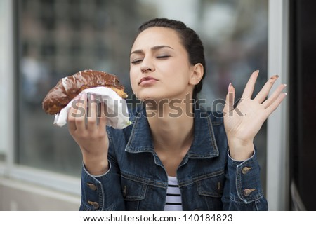 hungry girl eating a donut with chocolate outdoors - stock photo