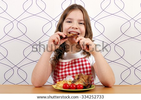 hungry girl eating chicken wings  - stock photo