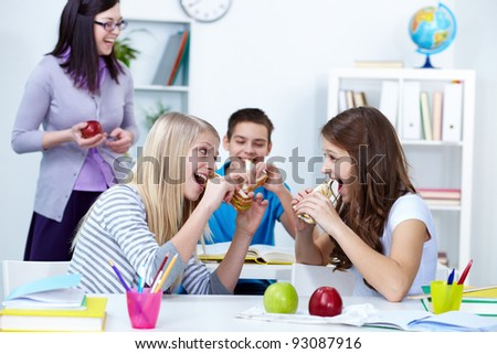 Hungry girls eating sandwiches during break in college - stock photo