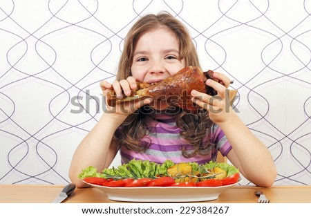 hungry little girl eating big turkey drumstick  - stock photo