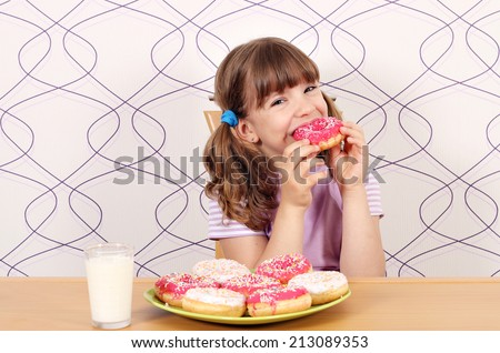 hungry little girl eating sweet donuts - stock photo