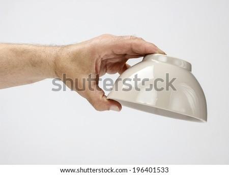 Hungry man holding empty bowl - stock photo