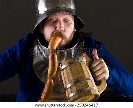 Hungry man in medieval suit  - stock photo