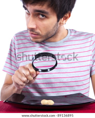 Hungry man looking to a peanut with a magnifying glass - stock photo