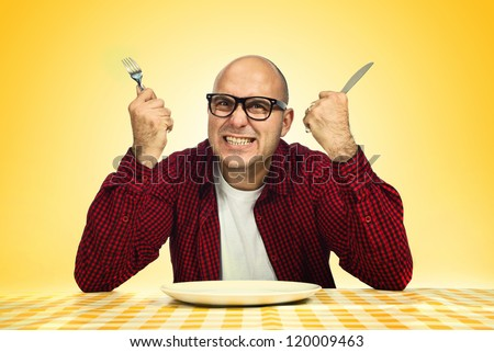 Hungry man sitting at dinner table with fork and knife raised. - stock photo