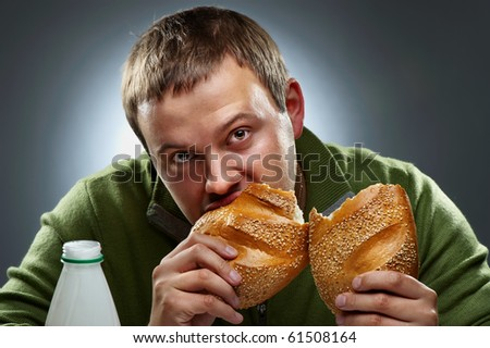 Hungry man with mouth full of bread - stock photo