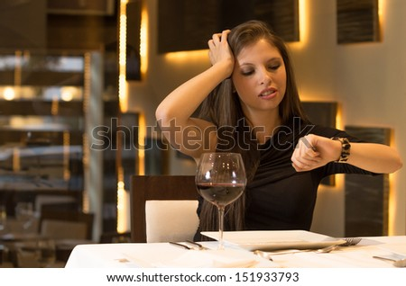 Hungry woman is waiting in a restaurant - stock photo