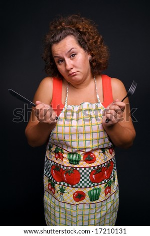 hungry woman over dark background - stock photo