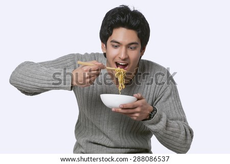 Hungry young man eating noodles - stock photo