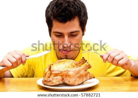 hungry young man waiting to eat freshly roasted whole chicken - stock photo