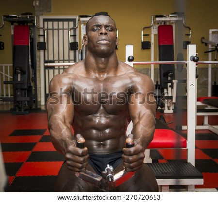Hunky muscular black bodybuilder working out in gym, exercising back on machine - stock photo