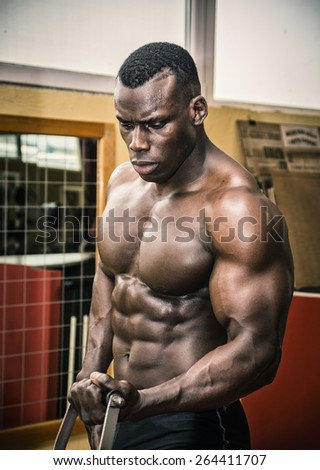Hunky muscular black bodybuilder working out in gym, exercising biceps on machine. - stock photo