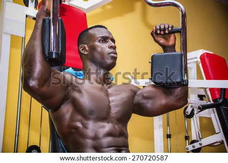 Hunky muscular black bodybuilder working out in gym, exercising pecs on machine - stock photo