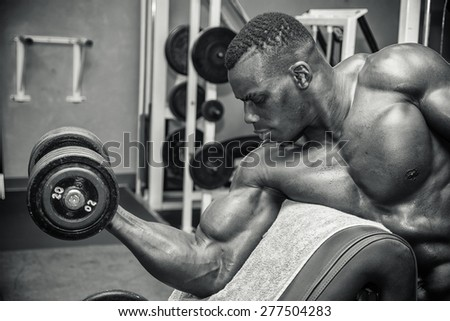 Hunky muscular black bodybuilder working out in gym, exercising with weights - stock photo