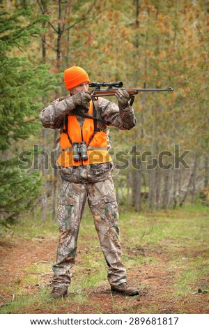hunter aiming deer rifle in forest - stock photo