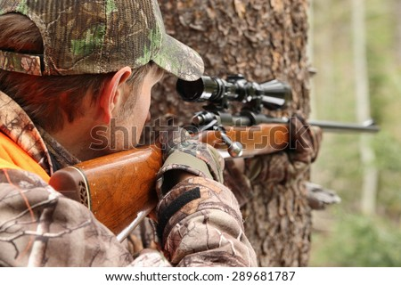 hunter aiming rifle in forest - stock photo
