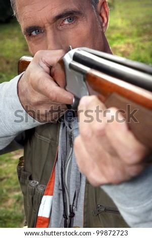 Hunter aiming with rifle - stock photo