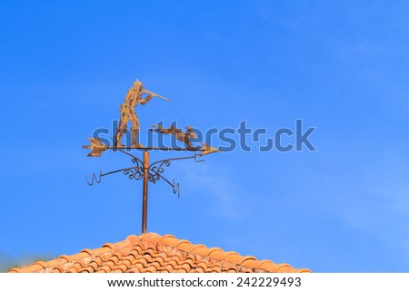 Hunter and  rabbit weather vane on roof and blue sky background - stock photo