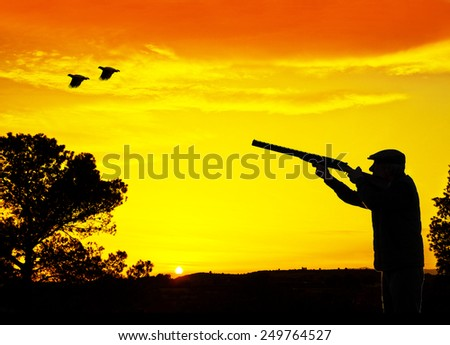 Hunter backlit in the field - stock photo