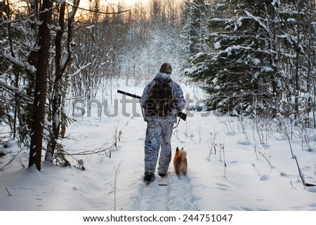 hunter comes out of the winter forest - stock photo