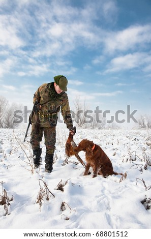 Hunter getting the pheasant from the dog during a winter hunting party. General open season scene - stock photo