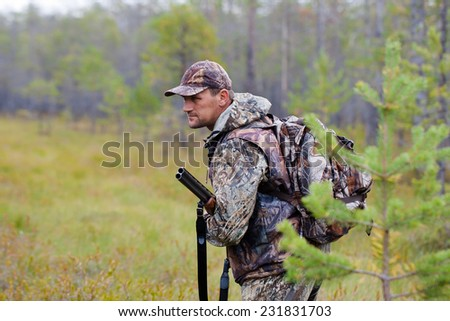 hunter holding a gun and waiting for prey - stock photo