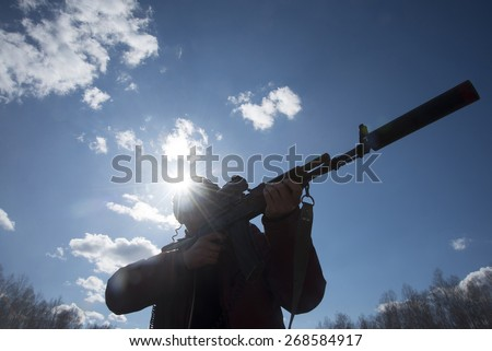Hunter holding rifle ready to shoot Silhouette Man look at  optical silencer against sun set rays light , blue sky with clouds and trees in forest Aiming at a target outdoor Modern Play laser tag  - stock photo