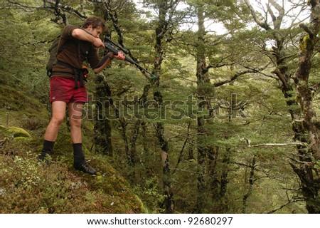 hunter in alpine tussock aiming rifle - stock photo