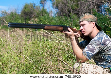 hunter in camouflage with a rifle at ready - stock photo