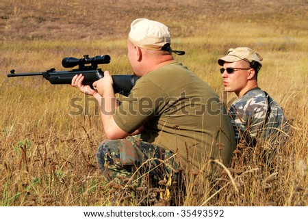 hunter in camouflage with rifle at ready - stock photo