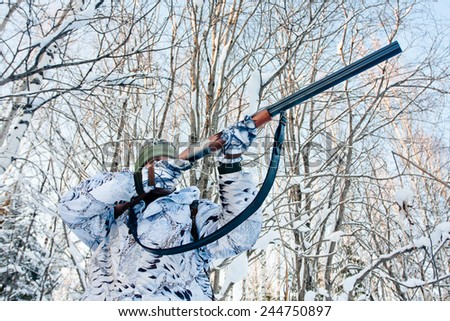hunter  in the winter camouflage shooting in winter forest - stock photo