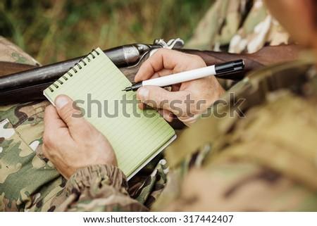 hunter loading his gun ans taking notes - stock photo