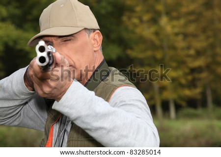Hunter looking down the barrel of a gun - stock photo