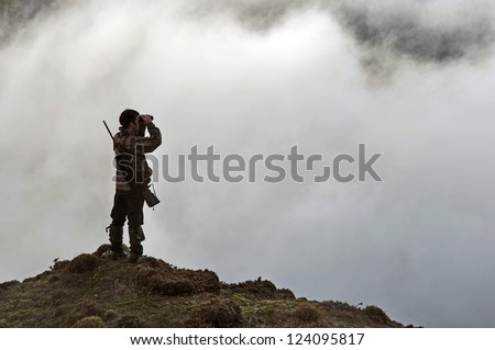 hunter looking for game animals such as chamois, deer or tahr, in  South Westland's Southern Alps, New Zealand - stock photo