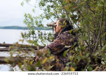 hunter looks through the binoculars at the river - stock photo