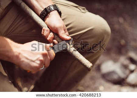 Hunter man with knife cut a wooden stick. Man lumberjack sharpens a wood stick for campfire in the forest. Close-up hand cutting tree branch outdoors. Man making timber log. - stock photo