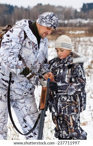 hunter shows his son how to charge the sporting gun - stock photo