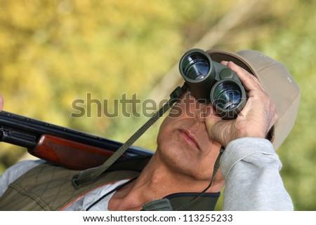 Hunter watching through binoculars - stock photo