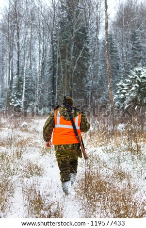 Hunter whistle with muzzle of gun in a snowy forest - stock photo