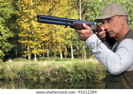 Hunter with a gun - stock photo